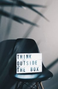 "A chair with a board saying ""think outside the box""—which is a great inspiration when it comes to website design."
