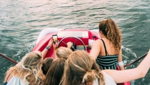 teens taking pictures while having fun in a boat.